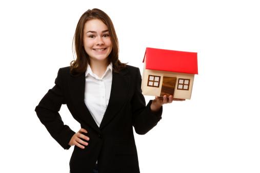 Girl holding model of house isolated on white
