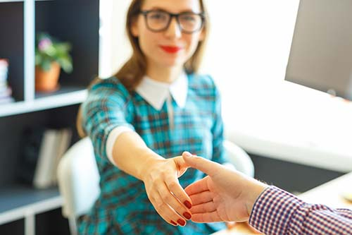Pretty young business woman with arm extended to handshake